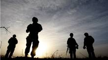 In this photo taken Tuesday, Jan. 26, 2010, Canadian soldiers from Task Force 3-09 Battle Group are seen silhouetted during operation Tazi, a village search and security operation in the Dand area of Kandahar Province, southern Afghanistan. (Kirsty Wigglesworth/AP/Kirsty Wigglesworth/AP)