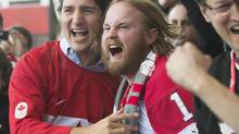 Liberal Leader Justin Trudeau, left, celebrates with Mike Burton in Montreal as they watch Team Canada score against Sweden in the gold medal Olympic men's hockey game on Feb. 23, 2014. (GRAHAM HUGHES/THE CANADIAN PRESS)