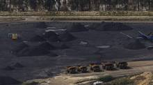 Trucks are seen in a coal mine, surrounded by floodwaters, in Baralaba, Queensland in this January 2, 2011 file photo. (Daniel Munoz/Reuters/Daniel Munoz/Reuters)