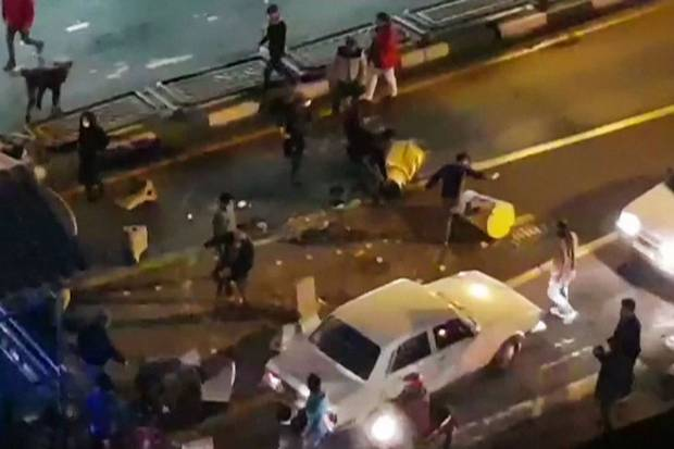 Dec. 30, 2017: An image grab taken from a handout video released by Iran's Mehr News agency reportedly shows a group of men pushing traffic barriers in a street in Tehran.