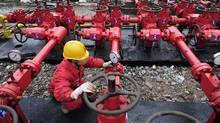 A worker performs a routine check to the valves at a shale gas appraisal well. (Reuters)