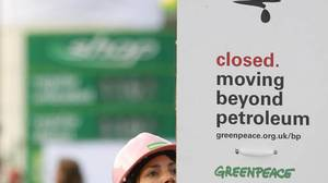An activist puts up a placard as Greenpeace blocks off a BP gasoline station during a protest in London.