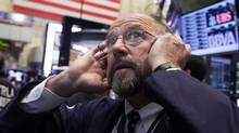 Trader Frederick Reimer tries to hear his phone on the floor of the New York Stock Exchange Thursday, Sept. 20, 2012. (Richard Drew/AP)