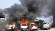 Cars set on fire by vandals burn on the first day of a two-day strike in Noida, a suburb of New Delhi, Feb. 20, 2013. (AP)