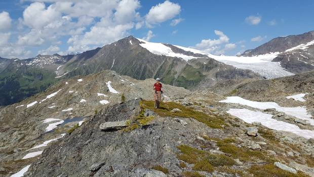 Annelies Ebner hiking in the Selkirk Mountains of British Columbia, the Durrand Glacier and Tumbledown Mountain behind her.