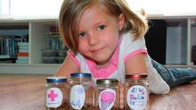 Kate Deveau, 5, divides her savings into baby food jars. Credit: Sarah Deveau