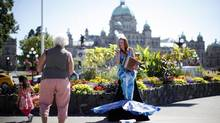 Mesmerizing Mermaid, Victoria's Hilarie Ann Higgins, blows a kiss to a passerby under a cloudless sky at the corner of Government and Belleview streets in Victoria July 25, 2013. (Chad Hipolito for The Globe and Mail)