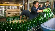 Steam Whistle worker Claudia Prietor loads empty beer bottles on a conveyor belt for the bottle washer. (Mark Spowart For The Globe and Mail)