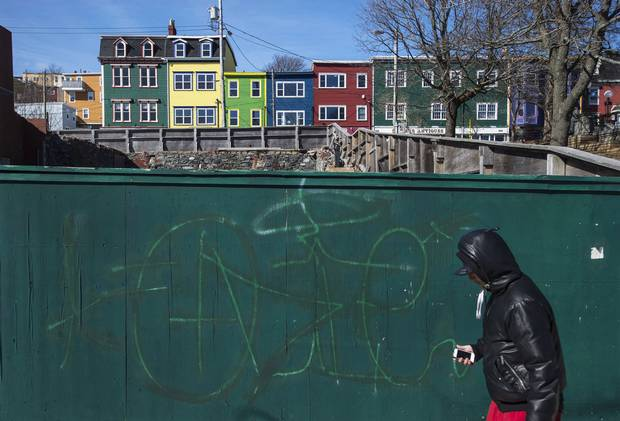 A man walks past a boarded-up construction site on Water Street in downtown St. John's.