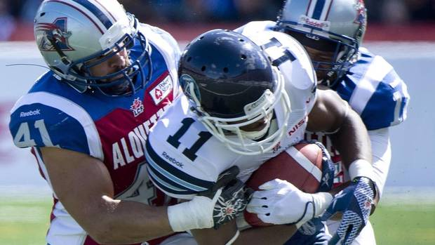 Montreal Alouettes' Shea Emry, left, and Geoff Tisdale, right, tackle Toronto Argonauts' Dontrelle Inman during first half CFL football action in Montreal, Sunday, September 8, 2013. (GRAHAM HUGHES/THE CANADIAN PRESS)