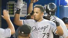 Chicago White Sox's Jose Abreu is congratulated in the dugout after he hit his second home run of the night off Toronto Blue Jays starting pitcher R.A. Dickey during seventh inning AL baseball game action in Toronto Friday June 27, 2014. (Fred Thornhill/THE CANADIAN PRESS)