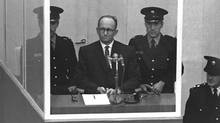 Adolph Eichmann stands in a protective glass booth flanked by Israeli police during his trial on April 5, 1961 in Jerusalem. (Getty Images)