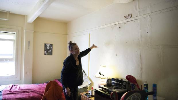 Roberta Wescenberg shows the water damage in her room that she says smelled and resembled urine.