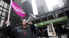 "A CUPE union member protests in front of the TD Bank on Bay Street in the financial district as part of the ""Occupy Toronto"" movement in Toronto, (MARK BLINCH/MARK BLINCH/REUTERS)"