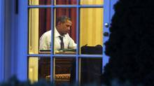 Seen from the Rose Garden, President Barack Obama works at his desk in the Oval Office of the White House in Washington, Jan. 27, 2014, ahead of Tuesday night's State of the Union speech. (Jacquelyn Martin/AP)