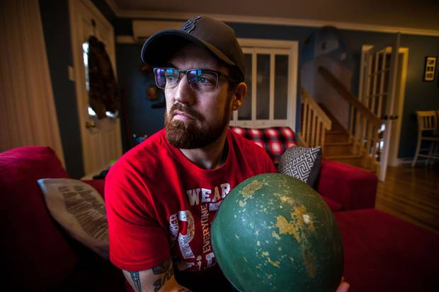 Mike McNell holds the dented helmet he was wearing when he hit an IED during a tour of Afghanistan.