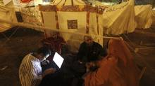 Protesters and activists talk and use a laptop in front of their tents during a sit-in at Tahrir Square in Cairo on Wednesday, Nov. 28, 2012. (AMR ABDALLAH DALSH/REUTERS)