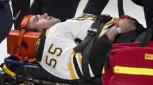 Boston Bruins' Johnny Boychuk is carried off the ice after taking a hit from Montreal Canadiens' Max Pacioretty during first period NHL hockey action Thursday, December 5, 2013 in Montreal. (PAUL CHIASSON/THE CANADIAN PRESS)