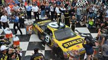 Marcos Ambrose gets out of his car in victory lane after winning the NASCAR Sprint Cup Series auto race at Watkins Glen. (Brian Czobat/AP)