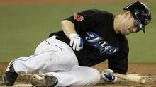 Toronto Blue Jays' Aaron Hill falls to the ground after fouling a ball off his foot during fifth-inning interleague baseball action against the Philadelphia Phillies in Toronto on Sunday. (Darren Calabrese)