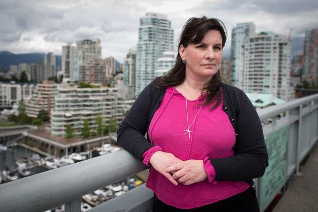 Karen Sawatzky, who has written her masters thesis on the impact of Airbnb on the rental market, stands for a photograph on Vancouver's Granville Street Bridge as condos fill the skyline behind her.