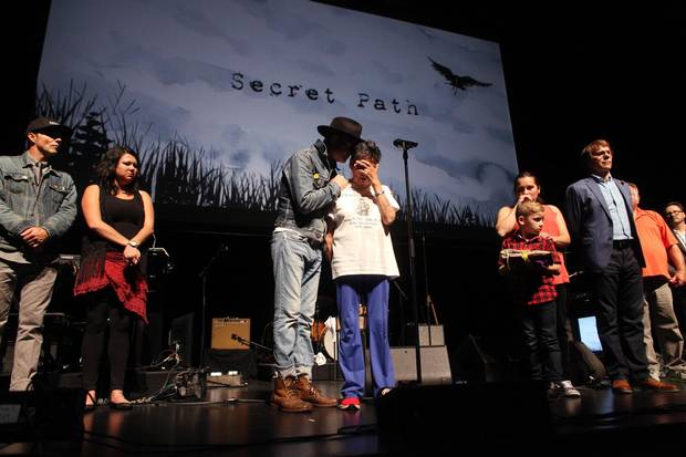 Gord Downie comforts Pearl Wenjack after she performed a traditional Anishinaabe healing song at the National Arts Centre.