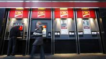 People walk past CIBC ATMs in Montreal. (CHRISTINNE MUSCHI/REUTERS)