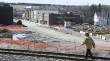 A woman walks the tracks in front of the downtown core in Lac Megantic, May 13, 2014. (Christinne Muschi/The Globe and Mail)
