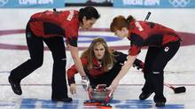 Canada's skip Jennifer Jones, center, delivers the rock to her sweepers Jill Officer, left, and Dawn McEwen during women's curling competition against Japan at the 2014 Winter Olympics, Saturday, Feb. 15, 2014, in Sochi, Russia. (Robert F. Bukaty/AP)