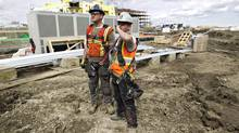 Temporary foreign workers Thomas Sutton, left, and Alan Williams from England, discuss the job as they work the construction of a new police station in Edmonton. (JASON FRANSON FOR THE GLOBE AND MAIL)