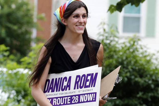 Danica Roem brings campaign signs as she greets voters while canvasing a neighbourhood in Manassas, Va., on June 21, 2017.