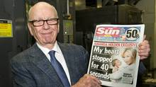 In this photo provided by News International (NI Group Ltd.) taken on Saturday Feb. 25, 2012, News Corporation Chairman and CEO Rupert Murdoch holds the first edition of The Sun on Sunday as it comes off the presses at Broxbourne, England. (Arthur Edwards/AP/Arthur Edwards/AP)