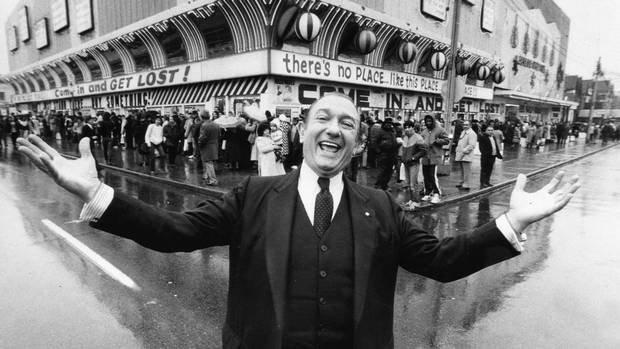 Entrepeneur Ed Mirvish throws his arms wide on Dec. 5, 1983 as hundreds of customers line up at his discount store on Bloor Street West for watches at five cents each.