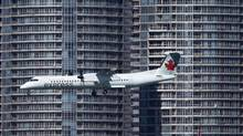 An Air Canada Express aircraft passes the Toronto skyline on approach for landing at the Toronto Island airport on Sept. 24, 2013. (MOE DOIRON/THE GLOBE AND MAIL)