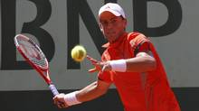 Vasek Pospisil of Canada returns the ball to Edouard Roger-Vasselin of France during the French Open tennis tournament at the Roland Garros stadium in Paris on Sunday. (GONZALO FUENTES)