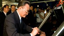 In this Sept. 7, 2009 photo released by First Solar, Chairman Wu Bangguo of the Standing Committee of the National People's Congress signs solar panel during an event in Phoenix.