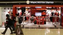 Shoppers walk past a Manchester United merchandise store at a mall in Singapore. (TIM CHONG/Reuters)