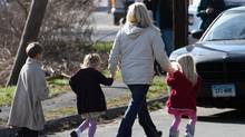 Parents walk away from the Sandy Hook Elementary School with their children following a shooting at the Newtown, Conn. school where authorities say a gunman opened fire, leaving 27 people dead, including 20 children, Friday, Dec. 14, 2012. (Frank Becerra Jr./The Journal News/Associated Press)