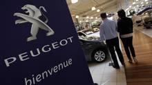 A salesman speaks with a customer at a Peugeot dealership in Marseille, France Feb. 1, 2013. (JEAN-PAUL PELISSIER/REUTERS)