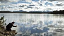 A member of Xeni Gwet'in First Nation stands at the edge of Fish Lake in British Columbia on Sept. 10, 2010. (JOHN LEHMANN/John Lehmann/The Globe and Mail)