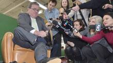 Finance Minister Jim Flaherty tries on a new pair of shoes at the Roots factory in Toronto, Wednesday, March 20, 2013. Flaherty is set to table the federal budget in the House of Commons on Thursday. (Nathan Denette/THE CANADIAN PRESS)