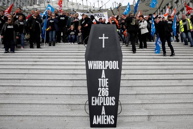 A makeshift coffin, reading 'Whirlpool killed 286 jobs in Amiens,' is seen as Whirlpool Amiens factory employees demonstrate outside the company headquarters at the financial and business district of La Defense, west of Paris, on April 18, 2017.