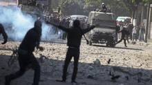Protesters and riot police clash Sunday in downtown Cairo. The Egyptian Justice Minister joined criticism of a sweeping edict issued Thursday by President Mohamed Morsi that exempted the President's decrees from judicial review until ratification of a constitution. (TARA TODRAS-WHITEHILL/NYT)