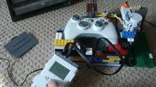 Guy Himber's Lego robot interacts with an Xbox 360 controller to perform repetitive actions in Gears of War 3. (Guy Himber)