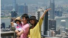 Tourists have their picture taken on Victoria Peak in Hong Kong on July 19, 2010. (MIKE CLARKE)