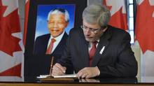 Prime Minister Stephen Harper pens a message on Dec. 6, 2013, in the book of condolence set up after the passing of Nelson Mandela. Mr. Harper has invited his predecessors to join him in attending a memorial for former South African president. (Adrian Wyld/The Canadian Press)