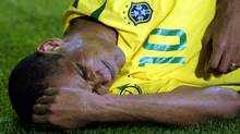 Brazilian midfielder Rivaldo lies on the pitch after being hit by a ball, kicked at him by Turkey's Hakan Unsal, during the World Cup in 2002. The ball hit Rivaldo in the leg, but he went down clutching his face. (DESMOND BOYLAN/Reuters)