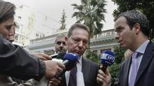 Greece's Finance Minister Yannis Stournaras, centre, is interviewed by reporters. After a meeting between Mr. Stournaras and the top brass of the Greek bank association on Monday, the ministry said Greek banks would report already-delayed six-month results a month later at the end of November. (YORGOS KARAHALIS/REUTERS)