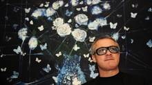"FILE PHOTO British artist Damien Hirst poses for photographers in front of his painting ""White Roses and Butterflies"" (2008), in London October 13, 2009. (Kieran Doherty/Reuters)"