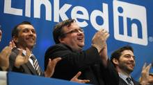 Linkedin founder Reid Garrett Hoffman (C) applauds with CEO Jeffrey Weiner (R) from the balcony after the opening bell at the New York Stock Exchange May 19, 2011 (MIKE SEGAR/Mike Seegar/Reuters)